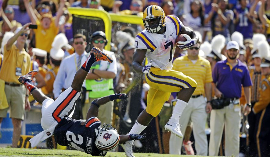 FILE - In this Sept. 19, 2015, file photo, LSU running back Leonard Fournette (7) gets away from Auburn defensive back Blake Countess (24) on a 40-yard touchdown run durin an NCAA college football game in Baton Rouge, La. No. 8 LSU is heading North to take on Syracuse in the Carrier Dome. It is the first time the Tigers will play in New York state since they beat Fordham at the Polo Grounds in 1942. (AP Photo/Gerald Herbert, File)