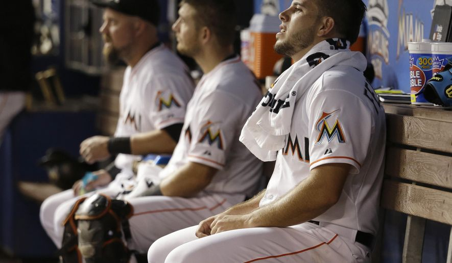Miami Marlins starting pitcher Jose Fernandez, right, sits in the dugout in the first inning of a baseball game against the Atlanta Braves, Friday, Sept. 25, 2015, in Miami. (AP Photo/Lynne Sladky)