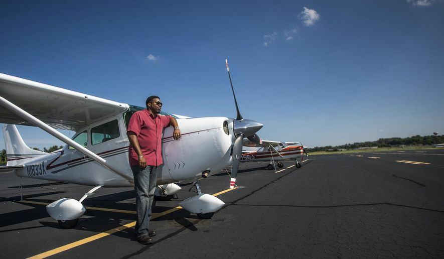 ADVANCE FOR SATURDAY, SEPT. 26, 2015, AT 12:01 A.M. EDT - Theron Burton, an IT business owner and pilot, poses near his plane at the Greenville Downtown Airport in Greenville, S.C., Tuesday, Sept. 1, 2015. Burton and Greenville pilot Clint Thompson have launched an effort to create a network group of other minority pilots throughout the Southeast. (Mykal McEldowney/The Greenville News via AP) NO SALES; MANDATORY CREDIT
