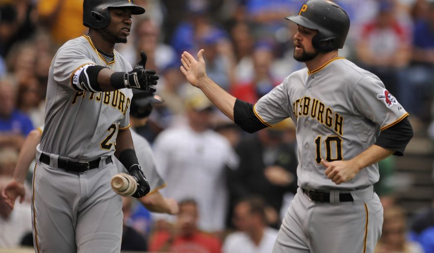 Pittsburgh Pirates' Jordy Mercer (10) celebrates with teammate Gregory Polanco (25) after scoring on a Gerrit Cole single during the third inning of a baseball game against the Chicago Cubs, Friday, Sept. 25, 2015, in Chicago. (AP Photo/Paul Beaty)