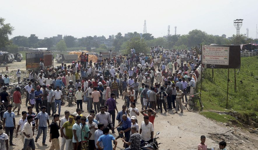 Nepalese people and Madhesi party leaders block a bridge in Birgunj, a town on the border with India, around 300 kilometers (200 miles) east of Kathmandu, Nepal, Friday, Sept. 25, 2015. Nepal warns that shortages of gasoline and medicine will be severe soon as supplies from India are not arriving during protests at border crossings by hundreds of people angry about Nepal's new constitution. (AP Photo/Manish Paudel)