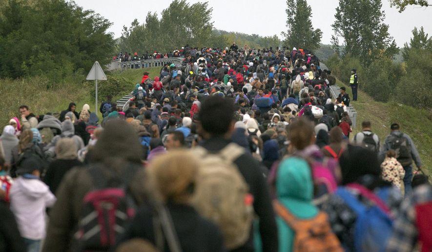 Migrants walk across a bridge in Botovo, Croatia, near the Hungarian border, Thursday, Sept. 24, 2015. (AP Photo/Darko Bandic) ** FILE **