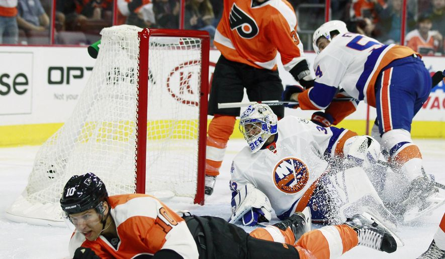 Philadelphia Flyers' Brayden Schenn, left, slides past the goal crease after scoring past New York Islanders goalie Christopher Gibson as Flyers' Chris Porter, rear, reacts early in the second period of a preseason NHL hockey game, Friday, Sept. 25, 2015, in Philadelphia. (AP Photo/Tom Mihalek)