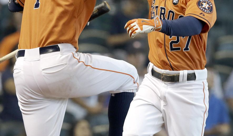 Houston Astros' Carlos Correa (1) and Jose Altuve (27) celebrate Altuve's solo home run against the Texas Rangers in the third inning of a baseball game Saturday, Sept. 26, 2015, in Houston. (AP Photo/Pat Sullivan)