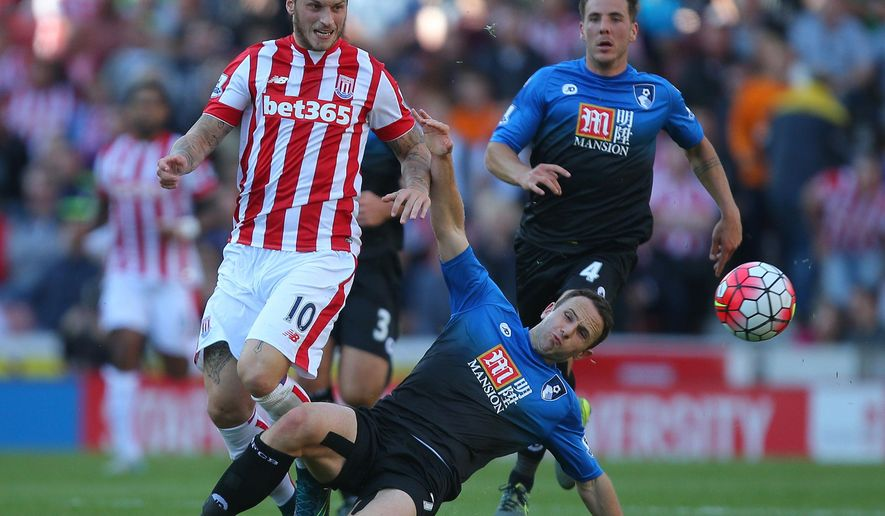 Stoke City's Marko Arnautovic, left, is tackled by AFC Bournemouth's Marc Pugh, center, during their English Premier League soccer match at the Britannia Stadium, Stoke, England, Saturday, Sept. 26, 2015. (Dave Thompson/PA via AP)     UNITED KINGDOM OUT       -     NO SALES      -      NO ARCHIVES