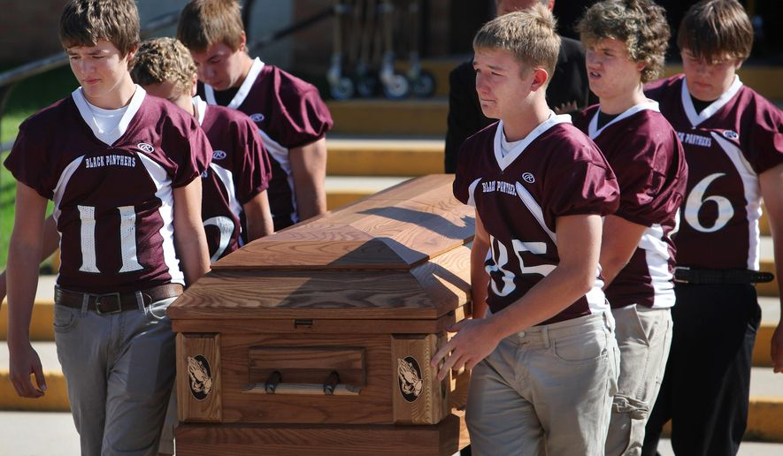 Casket bearers Payton Foxley (11) and Trevor Sprik (85) along with other teammates of the Platte-Geddes football team carry the casket of their friend, Michael Westerhuis, 16, outside of the Platte-Geddes Elementary School on Sat., Sept., 26, 2015 after the funeral service held in memory of the four Westerhuis children that died last week in Platte, S.D. Investigators believe Scott Westerhuis shot his wife and four children, then set the family home ablaze before shooting himself. (Jay Pickthorn/Argus Leader via AP)