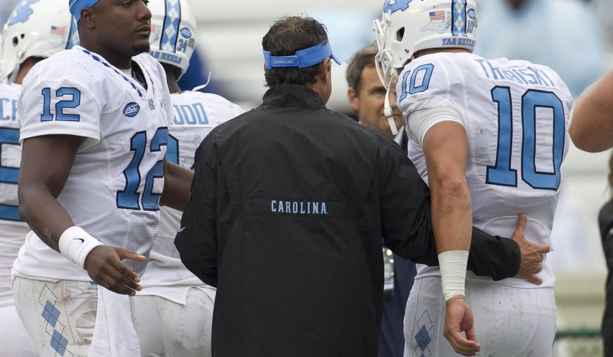 North Carolina coach Larry Fedora embraces quarterback Mitch Trubisky (10) as quarterback Marquise Williams looks on, after Trubisky connected with Bug Howard for a 10 yard touchdown in the fourth quarter against Delaware in an NCAA college football game, Saturday, Sept. 26, 2015 at Kenan Stadium in Chapel Hill, N.C. (Robert Willett/The News & Observer via AP) MANDATORY CREDIT