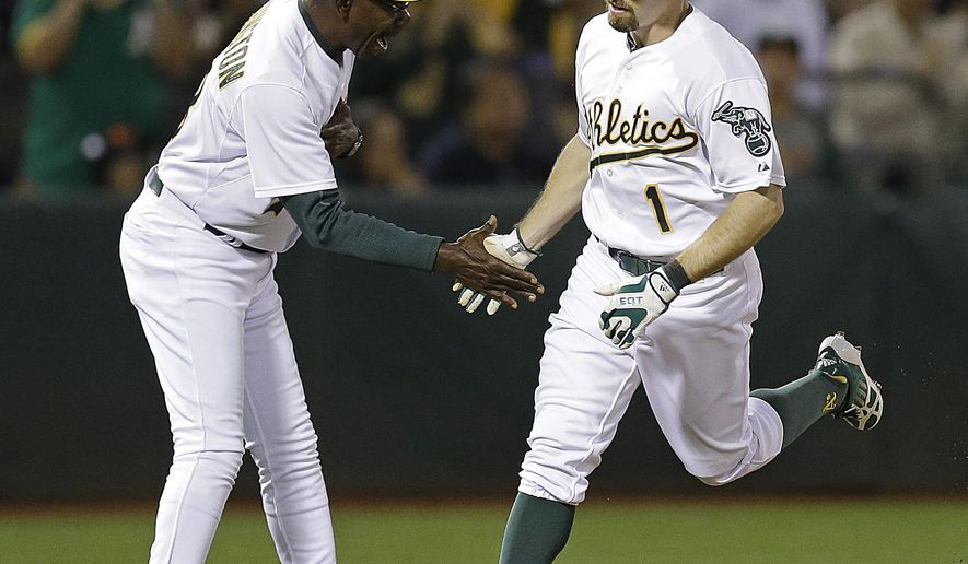 Oakland Athletics' Billy Burns, right, is congratulated by third base coach Ron Washington after hitting a home run against the San Francisco Giants during the third inning of a baseball game Friday, Sept. 25, 2015, in Oakland, Calif. (AP Photo/Ben Margot)