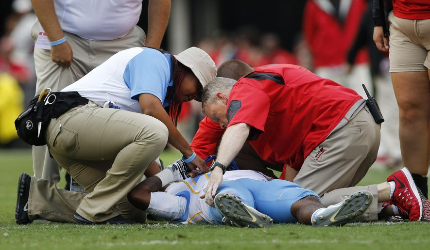 Members of the Southern and Georgia training staff tend to Southern wide receiver Devon Gales (33) after he was injured in the second half of an NCAA college football game against Georgia  Saturday, Sept. 26, 2015, in Athens , Ga. Gales was placed on backboard and taken off the field on a cart. (AP Photo/John Bazemore)