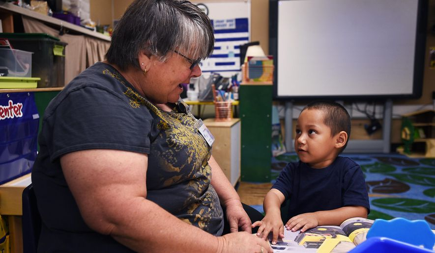 Teacher Lory Rehne, left, reads a book with pre-kindergarten student Junior Alvarez at Booth Elementary School in Reno, Nev. on Aug. 27, 2015. (Jason Bean/The Gazette-Journal via AP)