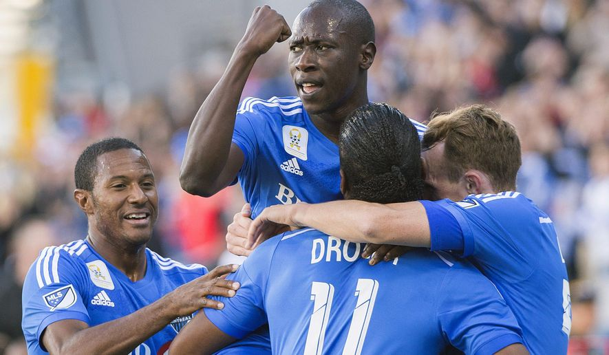 Montreal Impact's Didier Drogba (11) celebrates with teammates, from left, Patrice Bernier, Hassoun Camara and Wandrille Lefevre after scoring against D.C. United during first-half MLS soccer game action in Montreal, Saturday, Sept. 26, 2015. (Graham Hughes/The Canadian Press via AP) MANDATORY CREDIT