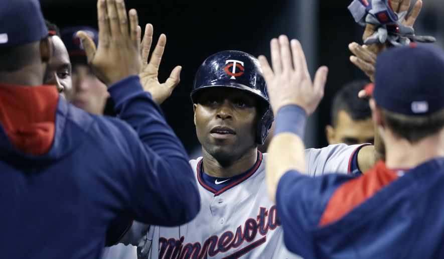 Minnesota Twins' Torii Hunter is congratulated after scoring during the seventh inning of a baseball game against the Detroit Tigers, Saturday, Sept. 26, 2015 in Detroit. (AP Photo/Carlos Osorio)