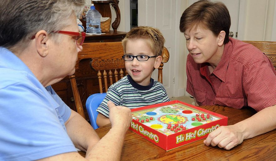 In this photo taken Sunday, Sept. 13, 2015, partners Reta Paul, left, and Erin Rush, who have been together for 18 years, play a board game with their adopted 5-year-old son Edward in their Quakertown, Pa., home. Between the U.S. visits of Pope John Paul II in October 1979 and Pope Francis in September 2015, there was a big shift in how Americans view marriage and family. (Art Gentile/The Intelligencer via AP)