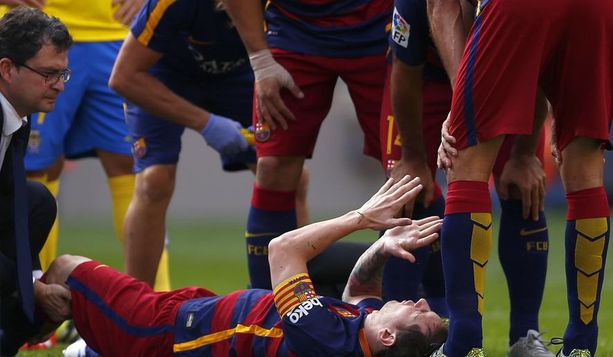 FC Barcelona's Lionel Messi, from Argentina, reacts after being injured,  during a Spanish La Liga soccer match against Las Palmas at the Camp Nou stadium in Barcelona, Spain, Saturday, Sept. 26, 2015. (AP Photo/Manu Fernandez)