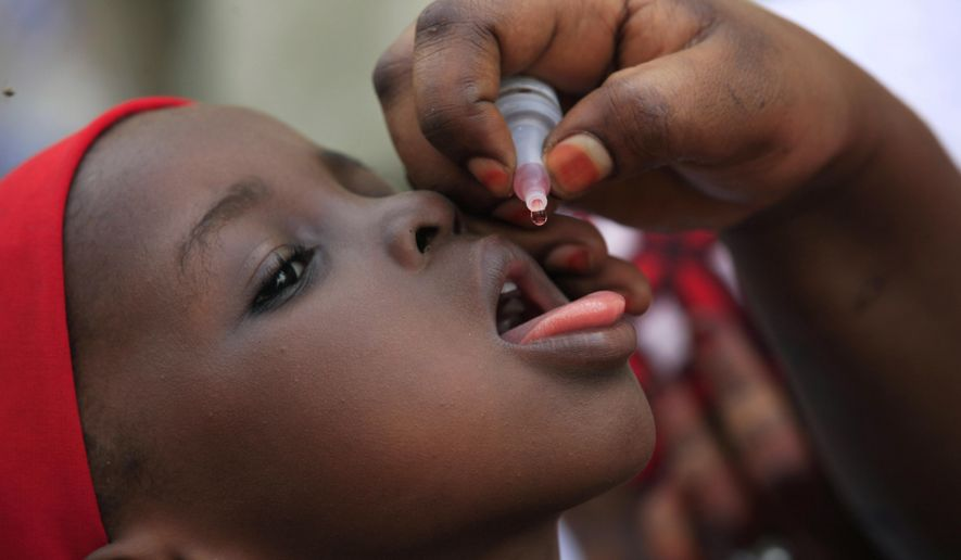 FILE- In this Sunday, April 13, 2014 file photo, a health official administers a polio vaccine to a child in Kawo Kano, Nigeria Polio is no longer endemic in Nigeria, the World Health Organization said late Friday, Sept. 25, 2015 leaving only Pakistan and its war-battered neighbor Afghanistan in the list of countries where the disease is prevalent. (AP Photo/ Sunday Alamba, File)