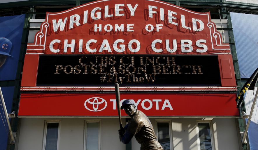 The sign outside Wrigley Field displays that the Chicago Cubs clinched a postseason berth before a baseball between the Pittsburgh Pirates and the Cubs, Saturday, Sept. 26, 2015, in Chicago. (AP Photo/Nam Y. Huh)
