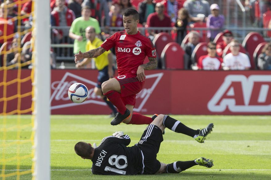 Chicago Fires' Jon Busch, bottom, tries to save the ball at the feet of Toronto FC 's Sebastian Giovinco during the first half of an MLS soccer game  in Toronto on Saturday, Sept. 26, 2015. (Chris Young/The Canadian Press via AP)