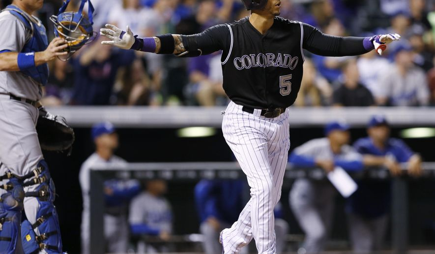 Colorado Rockies' Carlos Gonzalez, right, reacts after hitting a walkoff home run as Los Angeles Dodgers catcher A.J. Ellis looks on in the ninth inning of a baseball game Saturday, Sept. 26, 2015, in Denver. The Rockies won 8-6. (AP Photo/David Zalubowski)