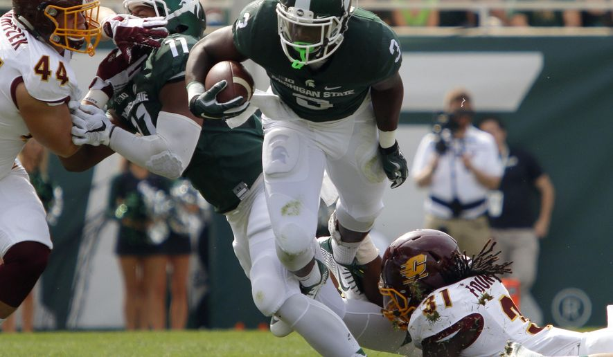 Michigan State's L.J. Scott, center, rushes against Central Michigan's Malik Fountain (31) and Mitch Stanitzek (44) as Michigan State's Jamal Lyles (11) blocks during the second quarter of an NCAA college football game, Saturday, Sept. 26, 2015, in East Lansing, Mich. (AP Photo/Al Goldis)