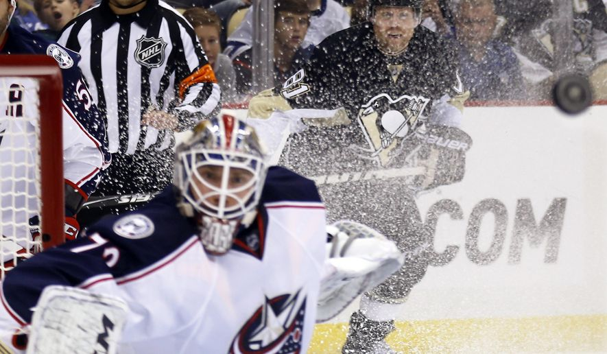 Pittsburgh Penguins' Phil Kessel, right, watches the puck fly past Columbus Blue Jackets goalie Sergei Bobrovsky after shooting during the second period of an NHL preseason hockey game, Saturday, Sept. 26, 2015, in Pittsburgh. (AP Photo/Keith Srakocic)