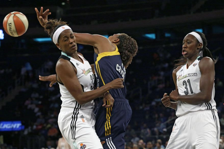 Indiana Fever forward Tamika Catchings, center, passes the ball past New York Liberty forward Swin Cash, left, and center Tina Charles during the first half of Game 1 of the WNBA basketball Eastern Conference finals, Wednesday, Sept. 23, 2015 at Madison Square Garden in New York.  (AP Photo/Mary Altaffer)