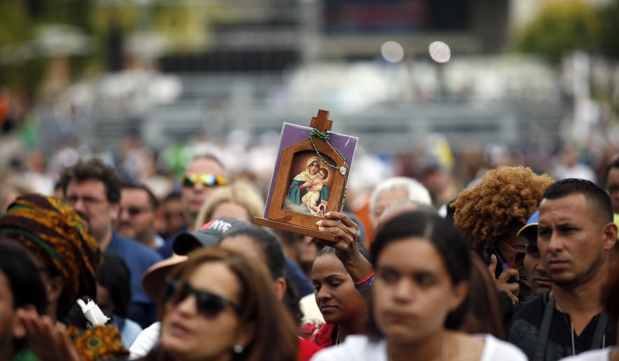 A woman holds an icon as she watches Pope Francis celebrate Mass on a large video monitor as people await the arrival of the pope at Independence Hall, Saturday, Sept. 26, 2015 in Philadelphia. (AP Photo/Alex Brandon)
