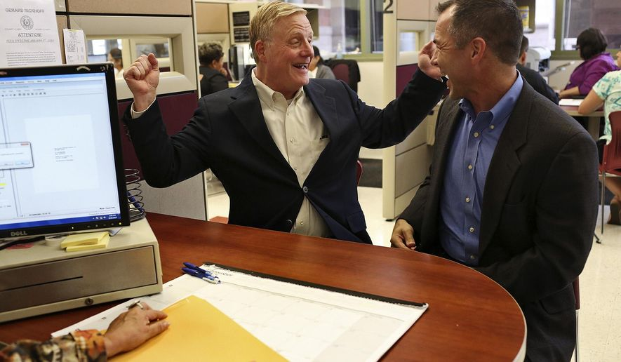 In this Friday, Sept. 25, 2015, Mark Phariss, left, and Victor Holmes celebrate getting their marriage license at the Bexar County Marriage License Office in San Antonio. The couple, who for the last several years has called Frisco home, was back in the Alamo City where they applied for and finally received the long-awaited marriage license. (Lisa Krantz/The San Antonio Express-News via AP) RUMBO DE SAN ANTONIO OUT; NO SALES; MANDATORY CREDIT