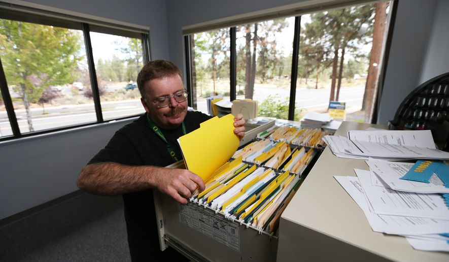 In this Thursday, Sept. 17, 2015 photo, Joseph Krassow files papers while working his shift at BBBI, A Human Resource Management Company, in Bend, Ore. Krassow, who has autism, said the job is a good fit with his talents, which include organization and math. (Andy Tullis/The Bend Bulletin via AP)  MANDATORY CREDIT