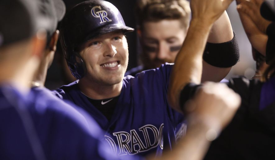 Colorado Rockies' Corey Dickerson is congratulated after hitting a solo home run off Los Angeles Dodgers starting pitcher Mike Bolsinger in the fourth inning of a baseball game Friday, Sept. 25, 2015, in Denver. (AP Photo/David Zalubowski)