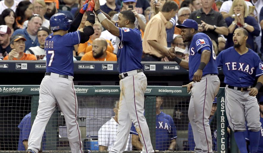 Texas Rangers' Shin-Soo Choo (17) is high-fived by Elvis Andrus as he is welcomed back to the dugout after hitting a two-run home run against the Houston Astros in the fourth inning of a baseball game Friday, Sept. 25, 2015, in Houston. (AP Photo/Pat Sullivan)
