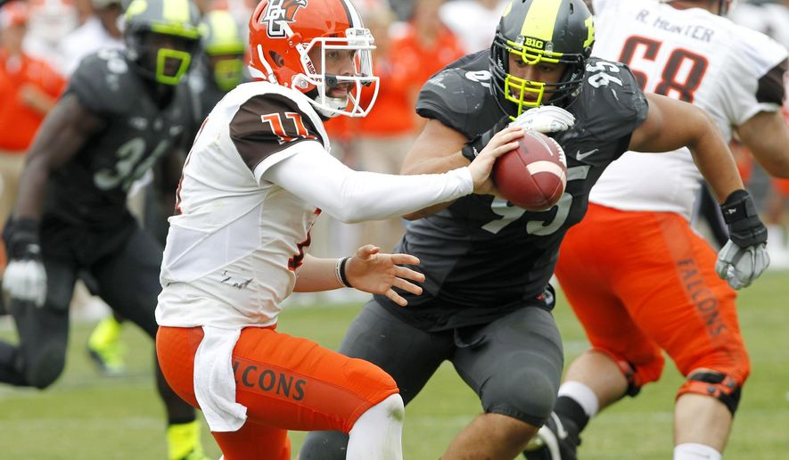 Bowling Green quarterback Matt Johnson (11) takes a shuffle pass ahead of the hit from Purdue's Evan Panfil during an NCAA college football game Saturday, Sept. 26, 2015, in West Lafayette, Ind. (John Terhune /Journal & Courier via AP) MANDATORY CREDIT; NO SALES; LOCAL TV OUT; LOCAL RADIO OUT; LOCAL INTERNET OUT