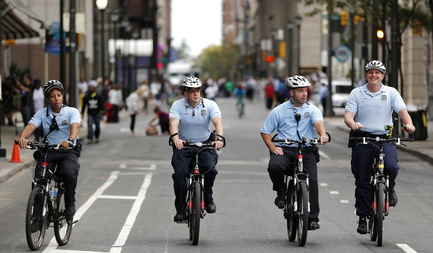 Philadelphia police officers ride bicycles while patrolling the downtown streets a day before the arrival of Pope Francis, Friday, Sept. 25, 2015, in Philadelphia. The pope wraps up his U.S. visit this weekend in Philadelphia, where he speaks in front of Independence Hall and celebrates Mass on the Benjamin Franklin Parkway to close out a big rally on Catholic families.  (AP Photo/Julio Cortez)