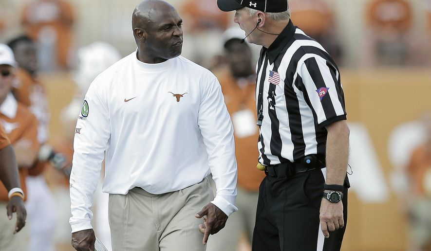 Texas head coach Charlie Strong, left, argues with an official during the second half of an NCAA college football game against Oklahoma State, Saturday, Sept. 26, 2015, in Austin, Texas. Strong received a penalty for the argument. Oklahoma State won 30-27. (AP Photo/Eric Gay)