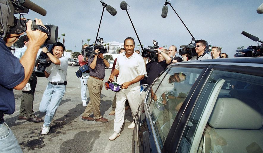 FILE - In this Thursday, May 15, 1997 file photo, O.J. Simpson is surrounded by journalists as he departs Santa Monica Superior Court in Santa Monica, Calif. On Saturday, Sept. 26, 2015, ABC News apologized for promoting as exclusive a Simpson story that covered ground reported 15 years ago by NBC. In a statement, ABC said it had the wrong impression that video from a deposition given by Simpson had not aired before at length. The deposition was connected to a civil lawsuit filed against him for the killings of his ex-wife, Nicole Simpson, and Ron Goldman. NBC's first reported on the video in 1999. (AP Photo/Nick Ut)