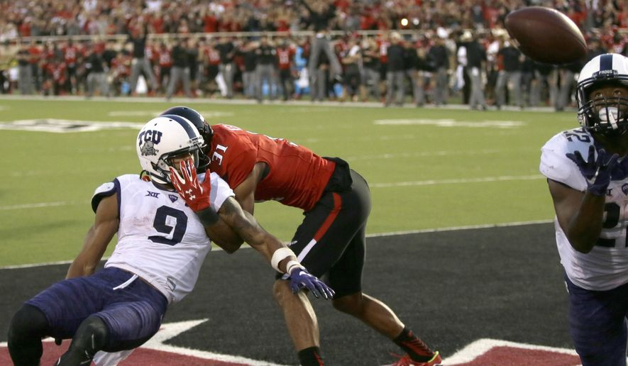 Texas Tech defensive back Justis Nelson (31) grabs TCU wide receiver Josh Doctson (9) after a pass was deflected to running back Aaron Green (22) for a touchdown during the fourth quarter of an NCAA college football game Saturday, Sept. 26, 2015, in Lubbock, Texas. TCU won 55-52. (AP Photo/LM Otero)