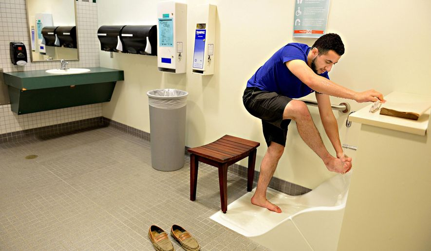 This photo taken June 1, 2015, shows Oregon State student Abdulrahman Alsulaim cleaning his feet as he performs Wudu, a cleaning ritual done before every prayer, at the foot wash station in the Valley Library on the Oregon State University Campus in Corvallis, Ore. This ritual is partly symbolic. If a believer does not have water available at the time, they can improvise with a smooth stone or sand.  (Amanda Cowan/The Corvallis Gazette-Times via AP)