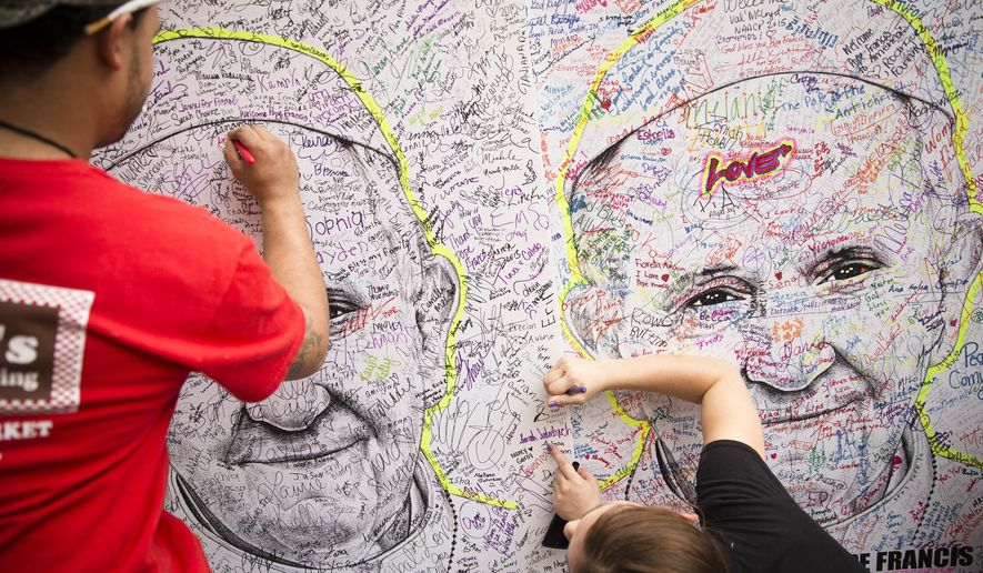 Pedestrians write messages and signatures on the likeness of Pope Francis, Friday, Sept. 25, 2015, in downtown Philadelphia. The pope wraps up his U.S. visit this weekend in Philadelphia, where he speaks in front of Independence Hall and celebrates Mass on the Benjamin Franklin Parkway to close out a big rally on Catholic families. (AP Photo/John Minchillo)