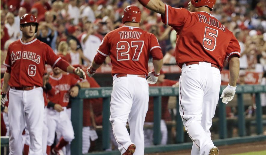Los Angeles Angels' Albert Pujols, right, celebrates his two run, home run against the Seattle Mariners during the first inning of a baseball game in Anaheim, Calif., Friday, Sept. 25, 2015. (AP Photo/Chris Carlson)