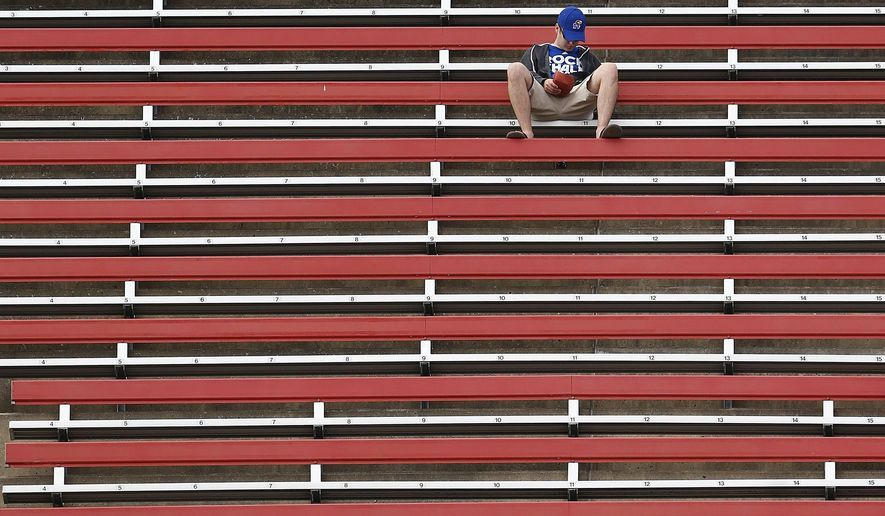 CORRECTS DATE TO SEPT. 26, NOT SEPT. 27 - A few fans sit among empty seats in the upper deck as Rutgers defeated Kansas 27-14 in an NCAA college football game Saturday, Sept. 26, 2015, in Piscataway, N.J. (AP Photo/Rich Schultz)