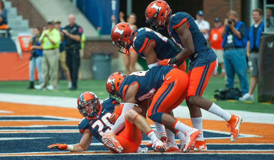 Illinois defensive back Clayton Fejedelem (20) is greeted by teammates after recovering a blocked punt in the end zone for a touchdown during the second quarter of an NCAA football game against Middle Tennessee Saturday, Sept. 26, 2015 at Memorial Stadium in Champaign, Ill.  (AP Photo/Bradley Leeb)