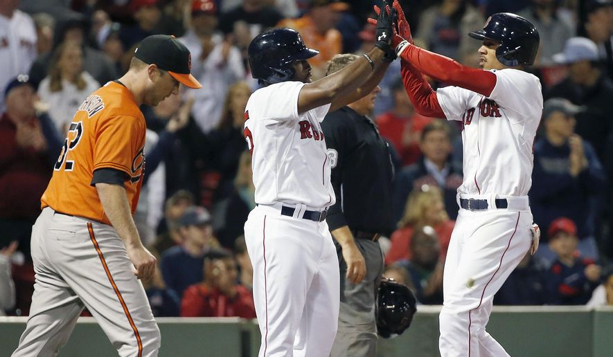 Boston Red Sox's Jackie Bradley Jr., center, and Xander Bogaerts, right, celebrate beside Baltimore Orioles' Steve Johnson, left, after scoring on a fielding error by Baltimore Orioles' Manny Machado during the eighth inning of a baseball game in Boston, Saturday, Sept. 26, 2015. The Red Sox won 8-0. (AP Photo/Michael Dwyer)