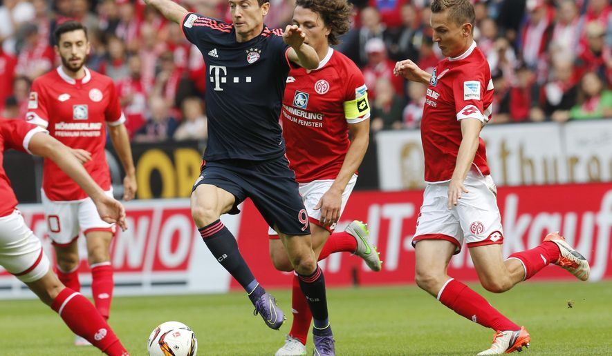Bayern's Robert Lewandowski, center, and Mainz's Pablo de Blasis, right, challenge for the ball during a German Bundesliga soccer match between FSV Mainz 05 and Bayern Munich in Mainz, Germany, Saturday, Sept. 26, 2015. (AP Photo/Michael Probst)