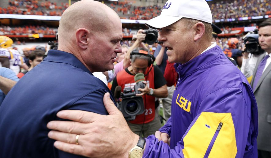 Syracuse head coach Scott Shafer, left, and LSU head coach Les Miles shake hands after an NCAA college football game on Saturday, Sept. 26, 2015, in Syracuse, N.Y. LSU won 34-24. (AP Photo/Mike Groll)
