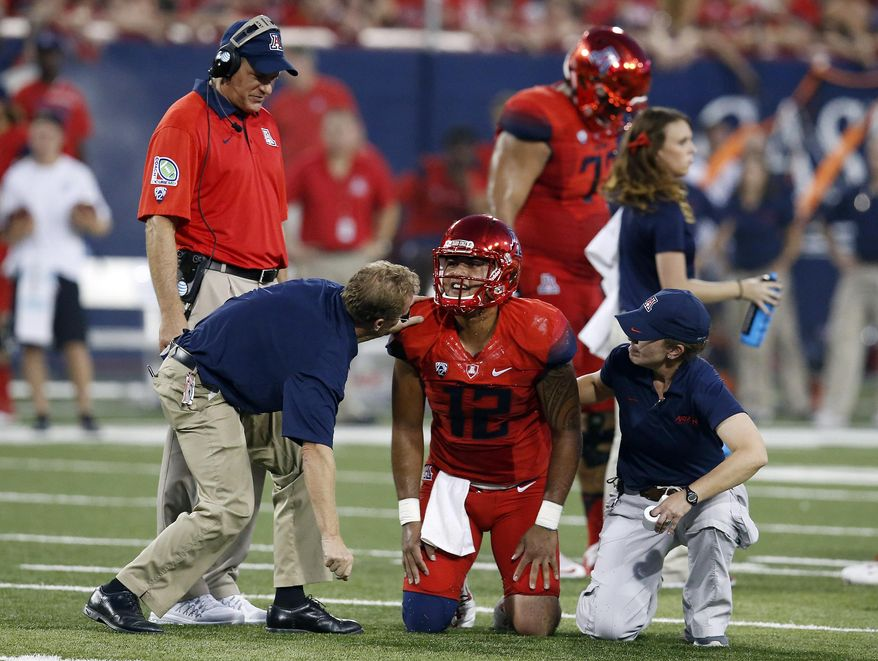 Arizona quarterback Anu Solomon (12) is checked by trainers during the first half of an NCAA college football game against UCLA, Saturday, Sept. 26, 2015, in Tucson, Ariz. (AP Photo/Rick Scuteri)