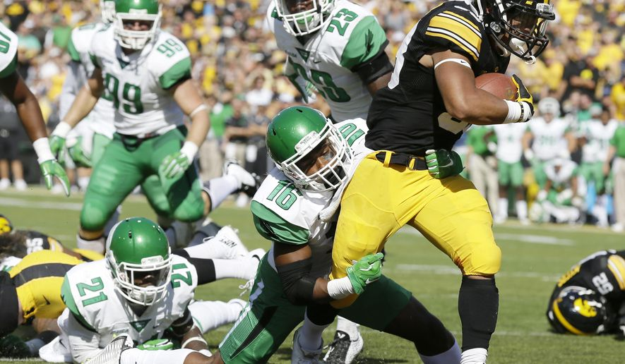 Iowa running back Jordan Canzeri breaks a tackle by North Texas defensive back Chad Davis (16) during a 10-yard touchdown run in the first half of an NCAA college football game, Saturday, Sept. 26, 2015, in Iowa City, Iowa. (AP Photo/Charlie Neibergall)