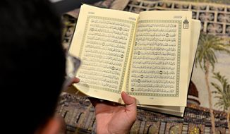 This photo taken June 1, 2015, shows Oregon State student Abdulrahman Alsulaim looking through the Qur'an while in a designated prayer area at the International Living Learning Center on campus in Corvallis, Ore. The Qur'an is the holy book for Muslims and is written in Arabic. (Amanda Cowan/The Corvallis Gazette-Times via AP)