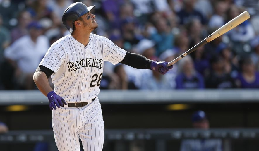 Colorado Rockies' Nolan Arenado follows the flight of his three-run home run off Los Angeles Dodgers starting pitcher Alex Wood in the fourth inning of a baseball game Sunday, Sept. 27, 2015, in Denver. (AP Photo/David Zalubowski)
