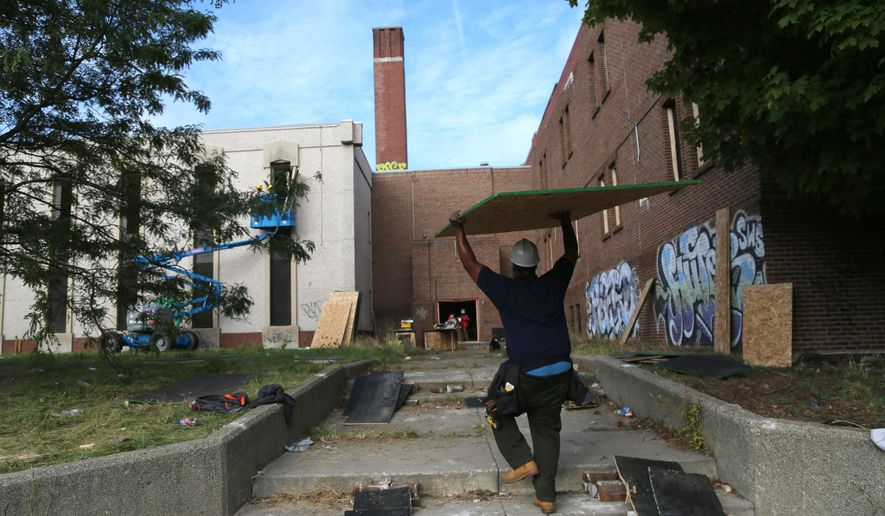 In this Friday, Sept. 25, 2015 photo, workers carry plywood to board up and secure the abandoned former Greenfield Park Elementary School  in Detroit.  City of Detroit has created Opportunity Detroit Youth Board-up, in collaboration with Jenkins Construction,  Building Trades Unions, and Detroit Employment Solutions to help young adults learn trade skills to be able to join the work force that is driving the rebuilding of the city of Detroit. (Jessica J. Trevino/Detroit Free Press via AP)  DETROIT NEWS OUT; TV OUT; MAGS OUT; NO SALES; MANDATORY CREDIT DETROIT FREE PRESS