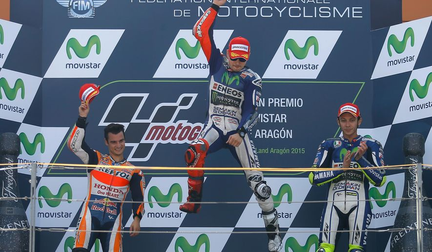 Moto GP rider Jorge Lorenzo of Spain jumps celebrating on the podium after winning  the Aragon Motorcycle Grand Prix at the Aragon Motorland racetrack in Alcaniz, Spain, Sunday, Sept. 27, 2015. At left is second placed Dani Pedrosa of Spaint and at right is third placed Valentino Rossi of Italy. (AP Photo/Francisco Seco)