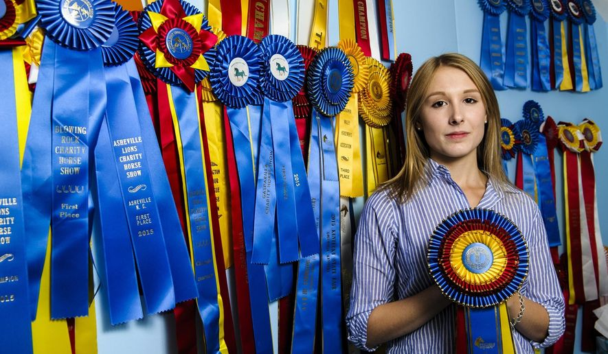 ADVANCE FOR MONDAY SEPT 28 AND THEREAFTER - In this Monday Sept 14, 2015 photo, Gretchen Halloran, a 16-year-old junior at George Washington High School, stands in her room, covered with ribbons from horse shows, at her home in Charleston, W. Va.  (Sam Owens/Charleston Gazette via AP)